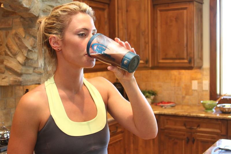 Mujer tomando batido de proteína - Fuente: Bodybuilding.com